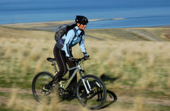 骑自行车的山妇女 免版税库存图片