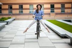 骑自行车的帽子的俏丽的女孩在街道 库存照片