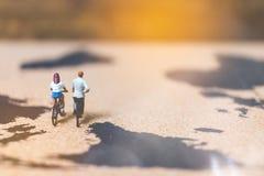 骑自行车的微型人旅客在世界地图, Traveli 免版税库存照片