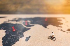 骑自行车的微型人旅客在世界地图, Traveli 图库摄影
