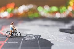 骑自行车的微型人旅客在世界地图 库存照片