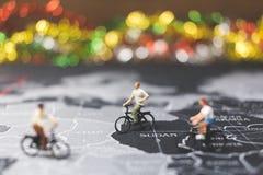 骑自行车的微型人旅客在世界地图 免版税库存图片