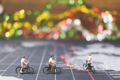 骑自行车的微型人旅客在世界地图 免版税图库摄影