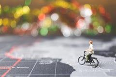 骑自行车的微型人旅客在世界地图 免版税库存照片
