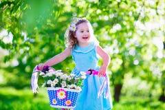 骑自行车的愉快的小女孩 免版税库存照片