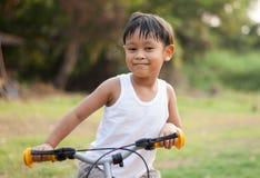 骑自行车的愉快的年轻亚洲男孩户外 免版税库存图片