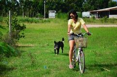 骑自行车的泰国妇女在庭院里 库存图片
