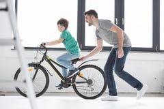 年轻骑自行车的父亲帮助的儿子 库存图片