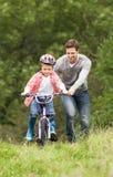 骑自行车的父亲教的儿子在乡下 库存照片