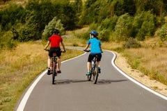 骑自行车的男孩女孩 免版税库存照片