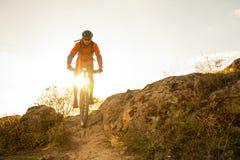 骑自行车的红色的骑自行车者在秋天岩石足迹在日落 极端体育和Enduro骑自行车的概念 库存照片
