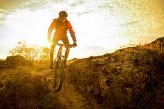 骑自行车的红色的骑自行车者在秋天岩石足迹在日落 极端体育和Enduro骑自行车的概念 免版税库存图片