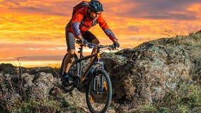 骑自行车的红色的骑自行车者在秋天岩石足迹在日落 极端体育和Enduro骑自行车的概念 免版税图库摄影