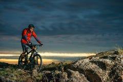 骑自行车的红色的骑自行车者在秋天岩石足迹在日落 极端体育和Enduro骑自行车的概念 图库摄影