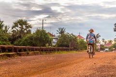 骑自行车的花衬衣的夫人 免版税库存图片