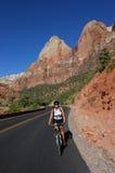 骑自行车的路妇女 免版税库存图片