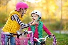 骑自行车的逗人喜爱的姐妹在城市公园在晴朗的秋天天 与孩子的活跃家庭休闲 佩带安全hemet一会儿的孩子 免版税图库摄影