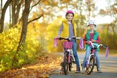 骑自行车的逗人喜爱的姐妹在城市公园在晴朗的秋天天 与孩子的活跃家庭休闲 佩带安全hemet一会儿的孩子 图库摄影