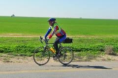 骑自行车的骑自行车者在一条开放路 库存照片