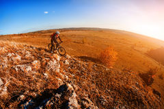 骑自行车的骑自行车者在山岩石足迹在日落 极其体育运动 图库摄影