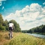 骑自行车的骑自行车者在河岸 被定调子的照片 库存图片