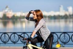 骑自行车的年轻红头发人妇女在堤防 户外激活人 体育生活方式 免版税库存图片