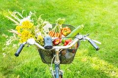 骑自行车篮子充满新鲜蔬菜和花 库存图片