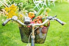 骑自行车篮子充满新鲜蔬菜和花 免版税库存图片