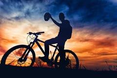 骑自行车者上升的盔甲剪影在竞争,赢取的马拉松以后 免版税库存照片