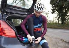 骑自行车者为坐在他的汽车背后的乘驾做准备 免版税库存图片