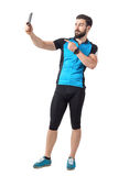 骑自行车者侧视图采取selfie和把手指指向的蓝色球衣T恤杉的电话照相机 图库摄影