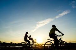 骑自行车者剪影有儿童行动的在日落背景 免版税库存图片
