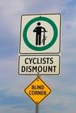 骑自行车者卸下与一次盲目的壁角警告的标志 免版税库存图片