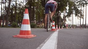 骑自行车者去围绕交通锥体 骑葡萄酒自行车的年轻英俊的人 循环在公园的运动的人 健康 免版税图库摄影
