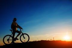 骑自行车者和一辆自行车剪影在天空背景 免版税库存图片