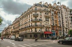 骑自行车者和交通在一条典型的街道有老大厦的在巴黎 库存照片