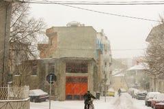 骑自行车者和步行者在多雪的波摩莱,保加利亚, 12月31日 免版税库存照片