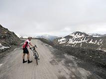 骑自行车者在他的自行车旁边站立在山口de la bonette col顶部在法国阿尔卑斯 免版税库存图片