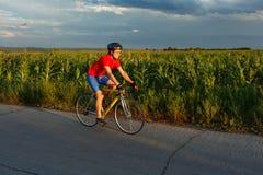 骑自行车者在沿领域的一辆路自行车乘坐 在背景中美丽的蓝天 库存图片