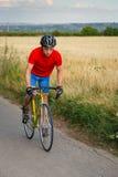 骑自行车者在沿领域的一辆路自行车乘坐 图库摄影
