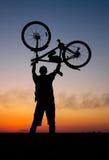 骑自行车者在背景拿着他的在他自己的自行车  免版税库存图片