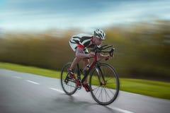 骑自行车者在自行车,速度作用,侧视图乘坐 免版税库存照片