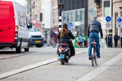 骑自行车者在阿姆斯特丹老中区的一个寒冷早期的春日  免版税库存图片