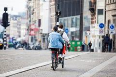 骑自行车者在阿姆斯特丹老中区的一个寒冷早期的春日  免版税库存照片