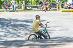 骑自行车者坐一辆BMX自行车在公园 免版税库存照片