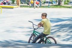 骑自行车者坐一辆BMX自行车在公园 免版税库存图片