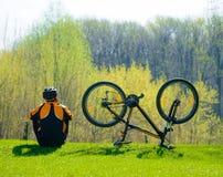 骑自行车者坐草在他的自行车附近 免版税库存照片