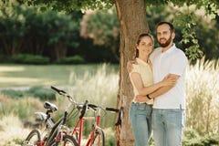 骑自行车者年轻夫妇拥抱得户外 免版税库存照片