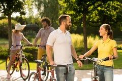 骑自行车者快乐的夫妇在公园 免版税库存图片