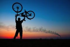 骑自行车者拿着他的在他自己的自行车 免版税库存图片